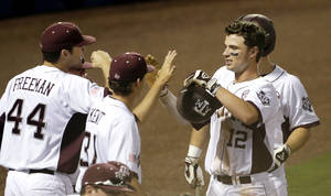 Photo - Texas A&M's Cole Lankford (12) is congratulated after scoring in the first inning of their Southeastern Conference Tournament NCAA college baseball game against Mississippi State at the Hoover Met in Hoover, Ala., Thursday, May 23, 2013. (AP Photo/Dave Martin)