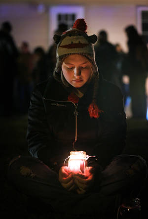 photo - Micayla Weber, of Waterloo, Iowa, holds a candle during a vigil for missing cousins Lyric Cook, 10, and Elizabeth Collins, 8, who vanished while riding bikes in Evansdale in July, Thursday, Dec. 6, 2012, in Evansdale, Iowa. Authorities announced Thursday they are confident bodies found in an isolated wildlife area are those of the two girls. (AP Photo/Charlie Neibergall)