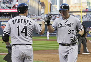Photo - Chicago White Sox's Paul Konerko, left, congratulates Adam Dunn after Dunn's solo home run off Minnesota Twins pitcher Kevin Correia in the third inning of a baseball game, Friday, Aug. 16, 2013, in Minneapolis. (AP Photo/Jim Mone)