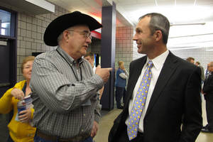 Photo - North Dakota Democratic convention delegate Dean Meyer, left, talks with the party's nominee for state agriculture commissioner, Ryan Taylor, during events Friday, March 28, 2014, in Fargo, N.D. (AP Photo/Dave Kolpack)
