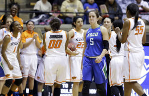 Photo - Florida Gulf Coast guard Sarah Hansen (5) walks off the court as Oklahoma State celebrates after winning 61-60 in overtime of a first-round game in the NCAA women's college basketball tournament in West Lafayette, Ind., Saturday, March 22, 2014.  (AP Photo/Michael Conroy)