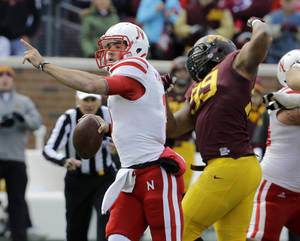 Photo - Nebraska quarterback Taylor Martinez, left, drops back for a pass during the second quarter of an NCAA college football game against Minnesota in Minneapolis, Saturday, Oct. 26, 2013. Minnesota beat Nebraska 34-23. (AP Photo/Ann Heisenfelt)