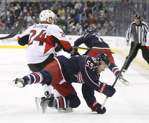Photo - Columbus Blue Jackets' Mark Letestu (55) is upended by Ottawa Senators' Stephane Da Costa (24), of France, during the first period of an NHL hockey game, Tuesday, Jan. 28, 2014, in Columbus, Ohio. (AP Photo/Mike Munden)
