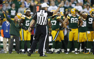 Photo -   Referee Jeff Triplette signals New Orleans Saints' possession, after a video review, during the second half of the Saints' NFL football game against the Green Bay Packers on Sunday, Sept. 30, 2012, in Green Bay, Wis. Saints' Darren Sproles appeared to fumble a kickoff but officials ruled that he was down by contact. Replays showed that the ball clearly came out but the Packers were out of replay challenges, leaving Packers fans screaming at the officials for the second week in a row. (AP Photo/Tom Lynn)