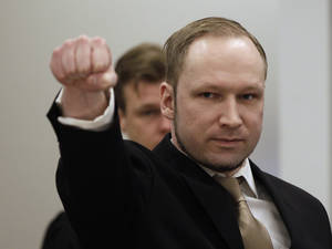 Photo -   Norwegian Anders Behring Breivik gestures as he arrives at a courtroom, to face terrorism and premeditated murder charges, Oslo, Norway, Monday, April 16, 2012. Breivik, who confessed to killing 77 people in a bomb-and-shooting massacre went on trial in Norway's capital Monday, defiantly rejecting the authority of the court. (AP Photo/Frank Augstein)