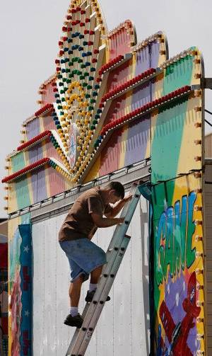 Photo - A man comes down a ladder after adjusting pieces on the front of this midway attraction Tuesday on the grounds of the Oklahoma State Fair. <strong>JIM BECKEL - THE OKLAHOMAN</strong>