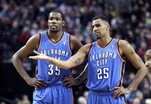 Photo - Oklahoma City Thunder's Kevin Durant, left, and Thabo Sefolosha, from Switzerland, talk during the first half of an NBA basketball game against the Portland Trail Blazers in Portland, Ore., Wednesday, Dec. 4, 2013. (AP Photo/Don Ryan)