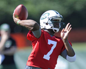 Photo - New York Jets quarterback Geno Smith throws a pass during NFL football training camp Friday, July 26, 2013, in Cortland, N.Y. (AP Photo/Bill Kostroun)