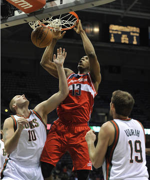 Photo - Washington Wizards' Kevin Seraphin (13) dunks the ball between Milwaukee Bucks' Joel Przybilla (10) and Beno Udrih (19) during the first half of an NBA basketball game Monday, Feb. 11, 2013, in Milwaukee. (AP Photo/Jim Prisching)