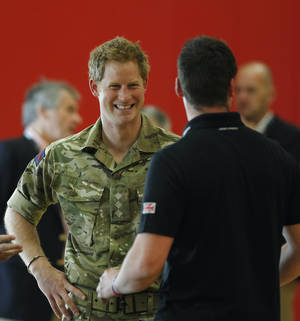 Photo - Britain's Prince Harry talks with members of the British Warrior Games Team who relaxed in a gymnasium before the opening of the 2013 Warrior Games, at the U.S. Olympic Training Center, in Colorado Springs, Colo., Saturday May 11, 2013. (AP Photo/Brennan Linsley, Pool)