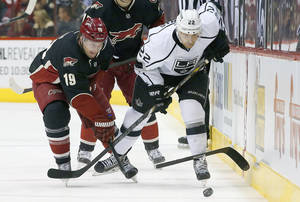 Photo - Phoenix Coyotes' Shane Doan (19) gets his stick broken by Los Angeles Kings' Trevor Lewis (22) during the first period of an NHL hockey game Tuesday, Jan. 28, 2014, in Glendale, Ariz. (AP Photo/Ross D. Franklin)