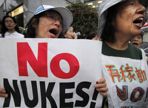 Photo - FILE - In this June 8, 2012 file photo, protesters shout slogans during an anti-nuclear plant rally in front of the Prime Minister's office in Tokyo shortly after Japanese Prime Minister Yoshihiko Noda said Japan must restart two nuclear reactors to protect the economy and people's livelihoods in a news conference. More than 20 months after a catastrophic nuclear disaster, massive protests against atomic energy and public opinion polls backing the phase-out of reactors, a pro-nuclear party won Japan's parliamentary election. The result left anti-nuclear proponents in shock Monday, Dec. 17, struggling to understand how the Liberal Democratic Party not only won, but won in a landslide. (AP Photo/Itsuo Inouye, File)