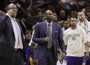 Photo -   Los Angeles Lakers' Kobe Bryant, center, wears street clothes during the first quarter of an NBA basketball game against the San Antonio Spurs, Wednesday, April 11, 2012, in San Antonio. Bryant is out with a left shin injury. (AP Photo/Eric Gay)