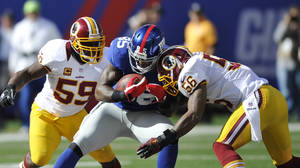 Photo -   New York Giants tight end Martellus Bennett (85) is tackled by Washington Redskins inside linebacker Perry Riley (56) as London Fletcher (59) closes in during the first half of an NFL football game Sunday, Oct. 21, 2012 in East Rutherford, N.J. (AP Photo/Bill Kostroun)