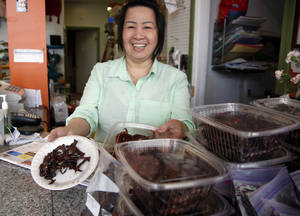 Photo - This March 13, 2014 photo shows Kimheng Chou showing off her homemade beef jerky at the Dessert Shop and Bakery in Lowell, Mass. Lowell now is home to one of the largest populations of Cambodians outside Cambodia. (AP Photo/Elise Amendola)