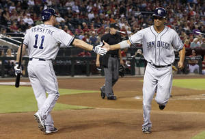 Photo - San Diego Padres' Will Venable, right, shakes hands with teammate Logan Forsythe (11) after scoring a run against the Arizona Diamondbacks in the first inning during a baseball game on Wednesday, Aug. 28, 2013, in Phoenix. (AP Photo/Ross D. Franklin)