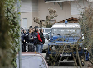 Photo - French police investigators stand outside a house in a residential area in Talloires, French Alps, Tuesday, Feb. 18, 2014, as part of an investigation into the grisly shooting deaths of a British-Iraqi man and three others nearly 18-months ago. French police announced Tuesday they have detained a 48-year old man, a resident of eastern France, in connection with the deaths. (AP Photo/Laurent Cipriani)