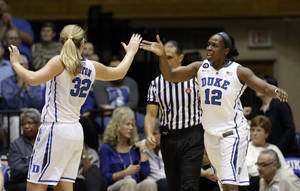 Photo - Duke's Tricia Liston (32) and Chelsea Gray (12) react following Gray's basket against Purdue during the second half of an NCAA college basketball game in Durham, N.C., Thursday, Dec. 5, 2013. Duke won 99-78. (AP Photo/Gerry Broome)