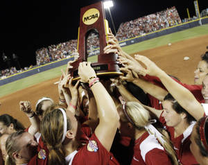 Photo - Oklahoma players raise the NCAA Championship trophy after winning the WCWS Final by defeatingTennessee 4-0 on June 4, 2013. Photo by KT KING, The Oklahoman