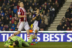 Photo - Liverpool's Luis Suarez, centre, celebrates after scoring his second goal past Stoke goalkeeper Jack Butland, bottom, during their English Premier League soccer match at the Britannia Stadium, Stoke, England, Sunday Jan 12, 2014. (AP Photo/Jon Super)