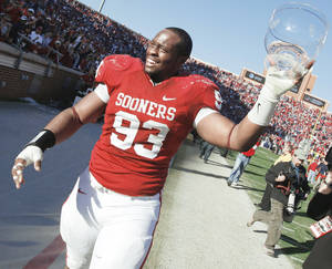 Photo - OU's Gerald McCoy celebrates with the trophy after the Bedlam college football game between OU and OSU  Saturday at the Gaylord Family-Oklahoma Memorial Stadium. Photo by Nate Billings, The Oklahoman