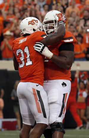 Photo - Oklahoma State's Jeremy Smith (31) celebrates a touchdown with Brandon Webb (51) during a college football game between the Oklahoma State University Cowboys (OSU) and the Lamar University Cardinals at Boone Pickens Stadium in Stillwater, Okla., Saturday, Sept. 14, 2013. Photo by Sarah Phipps, The Oklahoman