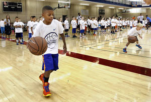 Photo - Jay Fair, 8, attends the  Kevin Durant Youth Basketball Camp on the campus of the University of Oklahoma (OU) on Friday, Aug. 9, 2013 in Norman, Okla. Photo by Steve Sisney, The Oklahoman