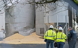 Photo - Department of Labor and Industries officials meet with emergency personnel at the site of collapsed grain silo in Roy, Wash.,Tuesday, Dec. 3, 2013.  A fire chief says a worker is presumed dead after the silo collapsed Monday and spilled tons of corn.  (AP Photo/The News Tribune,Peter Haley)