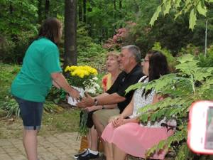 "Photo - Debbie Deakins, Grove Girl Scout Troop 1831 troop leader, gives a potted plant of daisies, as a remembrance of the Girl Scout Daisy Troop, to Mike and Julie Lewandowski, the parents of Jessica 'Jessie"" Lewandowski. (Grove Sun photo)"