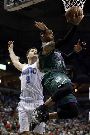 Photo - Milwaukee Bucks' Monta Ellis, right, shoots past Orlando Magic's Nikola Vucevic (9) during the second half of an NBA basketball game on Sunday, March 17, 2013, in Milwaukee. The Bucks won 115-109. (AP Photo/Morry Gash)