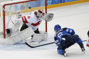Photo - Jenni Hiirikoski of Finland scores on Goalkeeper Florence Schelling of Switzerland to win the game 4-3 in overtime during the 2014 Winter Olympics women's ice hockey tournament at Shayba Arena, Wednesday, Feb. 12, 2014, in Sochi, Russia. (AP Photo/Petr David Josek)
