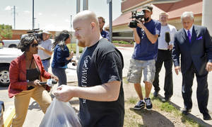 Photo - Attorney Irven Box walks with Justin Adams as he is released July 25 from the Oklahoma County jail in Oklahoma City on a  $100,000 bond.  Photo by Chris Landsberger, The Oklahoman <strong>CHRIS LANDSBERGER</strong>