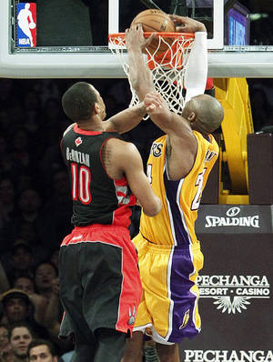 photo - Los Angeles Lakers guard Kobe Bryant (24) slam-dunks for two points as Toronto Raptors guard DeMar DeRozan (10) tries to block in overtime of an NBA basketball game in Los Angeles Friday, March 8, 2013. The basket put the Lakers ahead to stay as they won 118-116. (AP Photo/Reed Saxon)