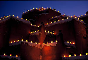 Photo - This undated image provided by New Mexico Tourism shows farolitos, which are candles in paper bags, flickering against the night sky atop Santa Fe's Inn at Loretto. The farolito lanterns, also called luminarias, are a New Mexico holiday tradition. (AP Photo/New Mexico Tourism Department)