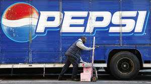 Photo - FILE - In this Feb. 9, 2012 file photo, Kandral McKenzie delivers Pepsi products in New York. PepsiCo reports quarterly earnings Wednesday, Oct. 16, 2013. (AP Photo/Mark Lennihan, File)