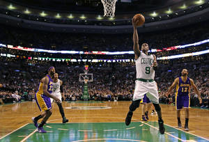 Photo - Boston Celtics guard Rajon Rondo (9) drives to the basket against the Los Angeles Lakers9during the second quarter of an NBA basketball game in Boston, Friday, Jan. 17, 2014. Rondo returned to the court for the first time this season, after undergoing surgery on his right knee. (AP Photo/Charles Krupa)