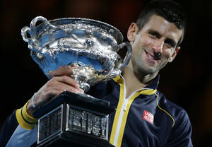 photo - Serbia's Novak Djokovic holds his trophy after defeating Britain's Andy Murray in the men's final at the Australian Open tennis championship in Melbourne, Australia, Sunday, Jan. 27, 2013. (AP Photo/Aaron Favila)