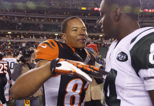 Photo - Cincinnati Bengals wide receiver Marvin Jones (82) meets with New York Jets wide receiver Stephen Hill (84) after the Bengals defeated the Jets 49-9 in an NFL football game, Sunday, Oct. 27, 2013, in Cincinnati. Jones caught four touchdown passes in the game. (AP Photo/David Kohl)