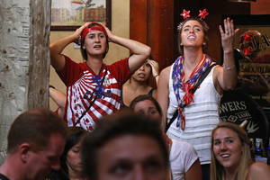 Photo - U.S. soccer fans at The Claddagh Irish Pub in Pittsburgh react as Portugal scores to tie the score at 2-2 with less than one minute remaining during a World Cup soccer match against the United States in Brazil Sunday, June 22, 2014. (AP Photo/Gene J. Puskar)
