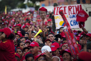 Photo -   Supporters of Venezuela's President Hugo Chavez, one holding up a mask representing Chavez, attend a campaign rally in Valencia, Venezuela, Wednesday, Oct. 3, 2012. Chavez is running for re-election against opposition candidate Henrique Capriles in presidential elections on Oct . 7. (AP Photo/Rodrigo Abd)