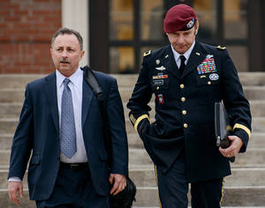 Photo - FILE - In this March 4, 2014, file photo, Brig. Gen. Jeffrey Sinclair, right, leaves the courthouse with his lawyers Richard Scheff, left, and Ellen C. Brotman, not pictured, following a day of motions at Fort Bragg, N.C. A military judge declined Monday, March 10, 2014, to dismiss sexual assault charges against Sinclair after reviewing what he said was evidence that political considerations influenced the military's handling of the case. (AP Photo/The Fayetteville Observer, James Robinson, File)