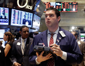 Photo - In this Wednesday, Sept. 25, 2013, photo, trader Robert McQuade works on the floor of the New York Stock Exchange. Worries about the U.S. economy and a looming budget battle in Washington kept global stock markets in check Thursday Sept. 26, 2013. (AP Photo/Richard Drew)