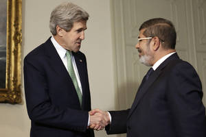 photo - U.S. Secretary of State John Kerry, left, shakes hands with Egyptian President Mohamed Morsi at the Presidential Palace in Cairo, Egypt on Sunday, March 3, 2013. U.S. Secretary of State John Kerry met with Egypt's president Sunday, wrapping up a visit to the deeply divided country with an appeal for unity and reform. The U.S. is deeply concerned that continued instability in Egypt will have broader consequences in a region already rocked by unrest. (AP Photo/Jacquelyn Martin, Pool)
