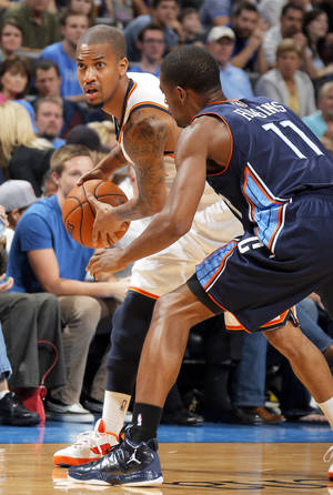Photo - Oklahoma City's Eric Maynor, left, tries to pass around Charlotte's Cory Higgins during the preseason game at Chesapeake Energy Arena on Tuesday. Photo by Sarah Phipps, The Oklahoman