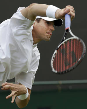 Photo - ADVANCE FOR WEEKEND EDITIONS, JUNE 21-22 - FILE - In this June 25, 2012, file photo, John Isner, of United States, serves to Alejandro Falla, of Colombia, during a first round men's singles match at the All England Lawn Tennis Championships at Wimbledon, England. (AP Photo/Alastair Grant, File)