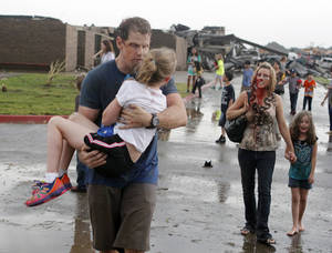 Photo - Teacher Ledonna Cobb walks with a student while husband Steve Cobb carries their daughter Jordan away from Briarwood Elementary school after a tornado destroyed the school in south OKC Oklahoma City, OK, Monday, May 20, 2013. Near SW 149th and Hudson. By Paul Hellstern, The Oklahoman