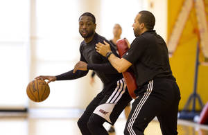 Photo - Miami Heat's Dwyane Wade, left, runs drills against David Fizdale during the team's practice session Sunday, May 5, 2013, as The Heat prepares to play the Chicago Bull in the upcoming NBA bsketball playoff series, in Miami. (AP Photo/J Pat Carter)