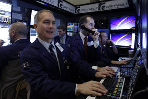 Photo - FILE - In this Monday, March 17, 2014, file photo, trader Timothy Nick, foreground left, works with colleagues in a booth on the floor of the New York Stock Exchange. Asian stock markets were subdued Wednesday March 19, 2014 ahead of the outcome of the Federal Reserve's first policy meeting under its new chief. (AP Photo/Richard Drew, File)