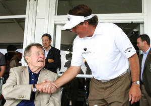 Photo - Phil Mickelson visits with former president George H.W. Bush after completing the third round of the Houston Open golf tournament, Saturday, March, 30, 2013, in Humble, Texas. (AP Photo/Patric Schneider)