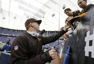 Photo - Cleveland Browns quarterback Brandon Weeden, left, signs autographs before an NFL football game against the Minnesota Vikings, Sunday, Sept. 22, 2013, in Minneapolis. (AP Photo/Charlie Neibergall)